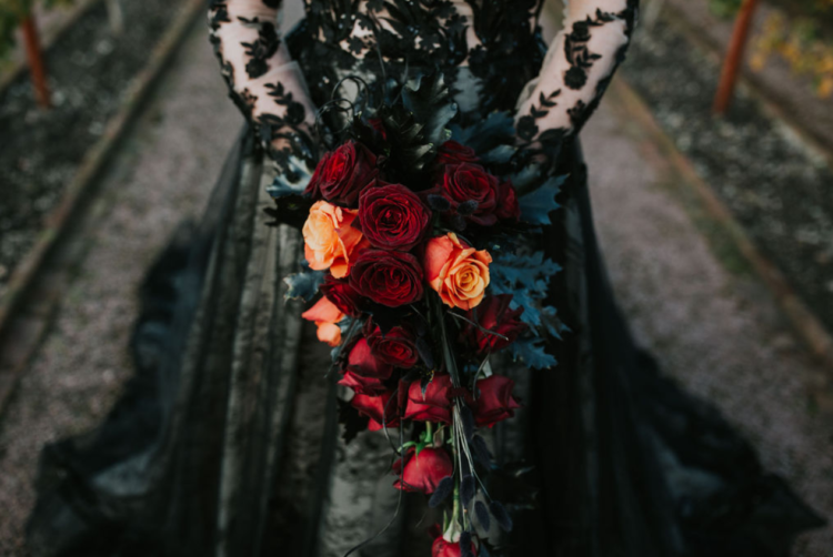 The bride was carrying a burgundy and orange wedding bouquet that was cascading