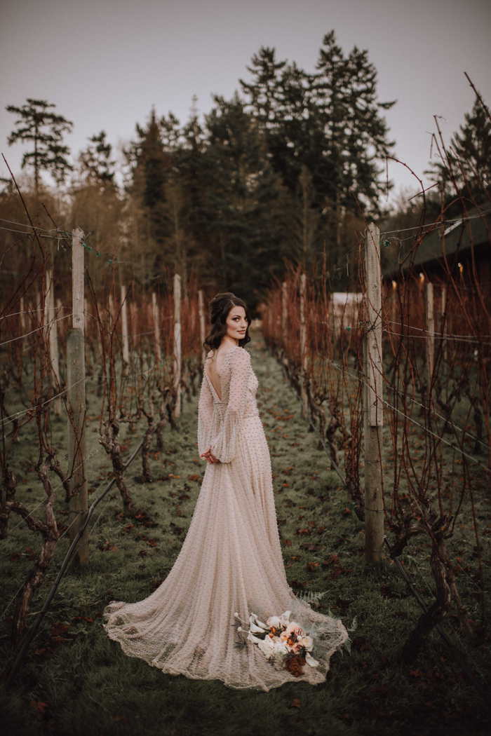 The bride was wearing a blush A-line wedding dress fully covered with pearls, a cutout back and long sleeves