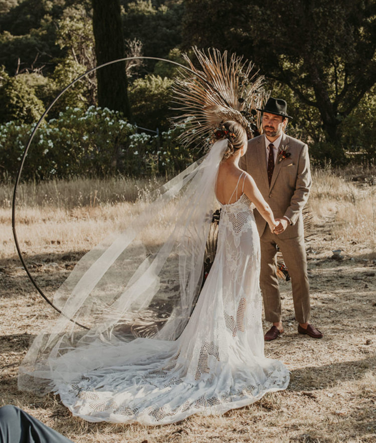 The bride was wearing a boho lace A-line wedding dress on spaghetti straps, with a train and a long veil