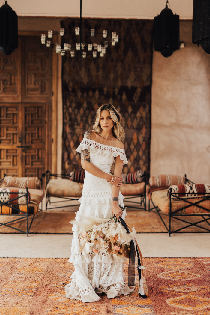 The bride was wearing an off the shoulder boho lace wedding dress with a layered necklace