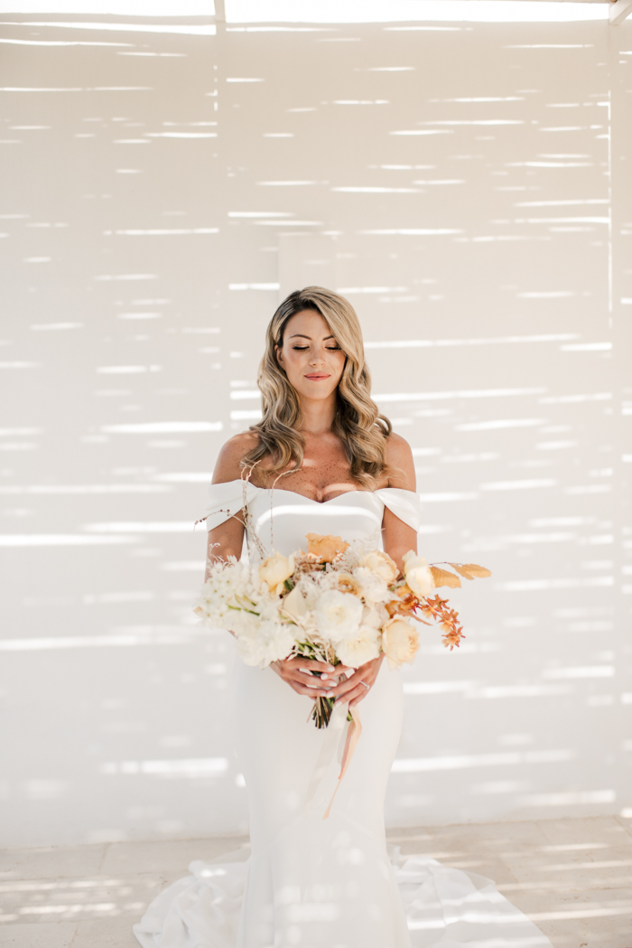The bride was wearing an off the shoulder mermaid wedding dress and carrying a creamy and rust bouquet