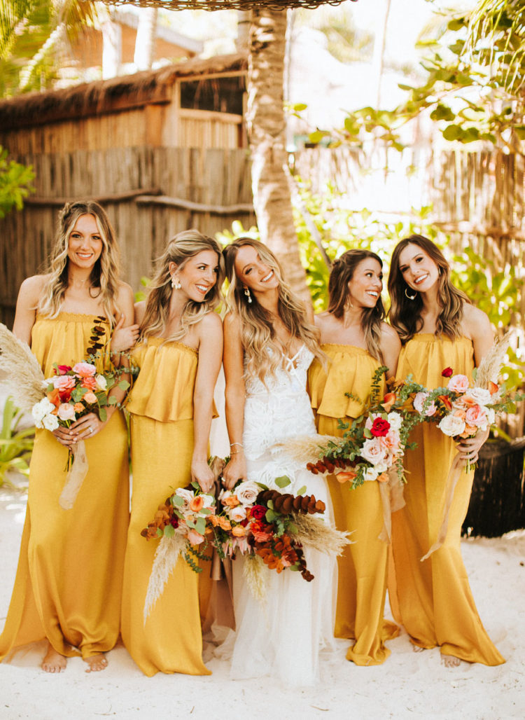 The bridesmaids were wearing marigold off the shoulder maxi dress and carrying bright bouquets