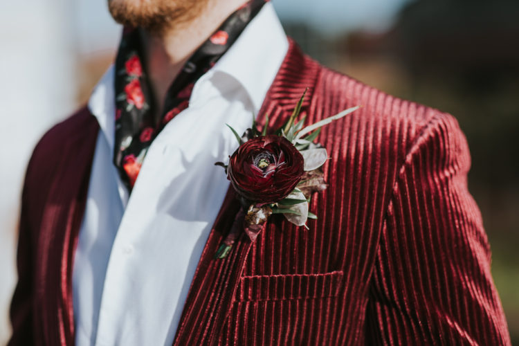 The groom wore a burgundy velvet blazer, a white shirt and a floral neck tie