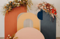 03 The wedding backdrop was a muted one, a cutout wooden backdrop with bright blooms and greenery