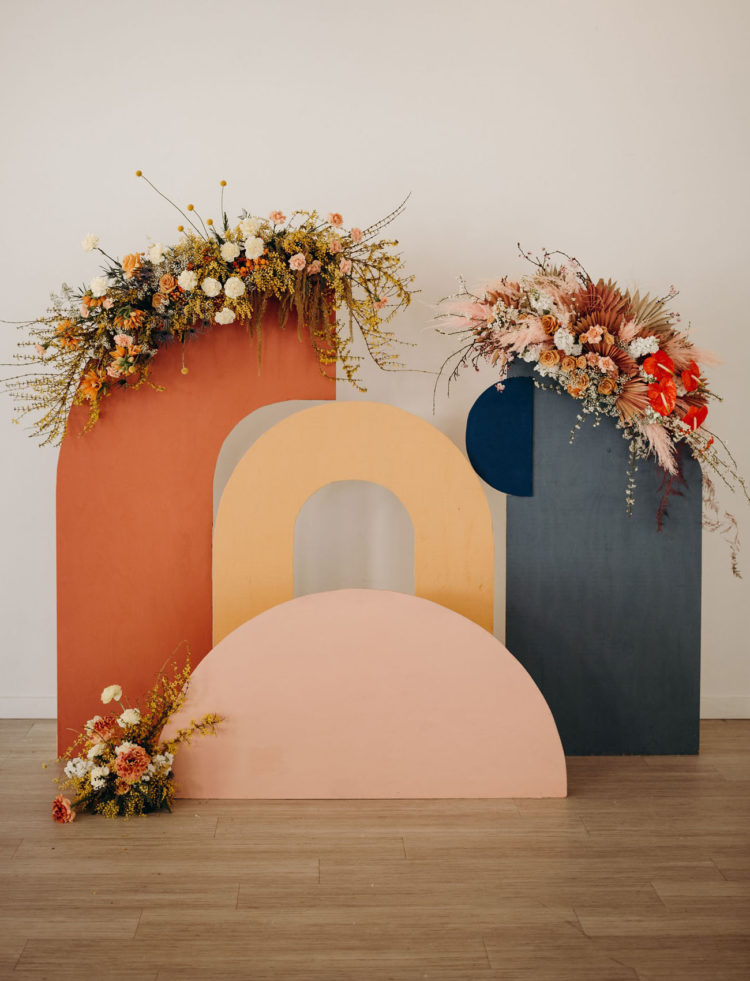 The wedding backdrop was a muted one, a cutout wooden backdrop with bright blooms and greenery