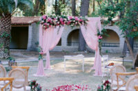 03 The wedding ceremony space was done with a bright pink wedding arch decorated with blooms and greenery, there were pink petals and lanterns