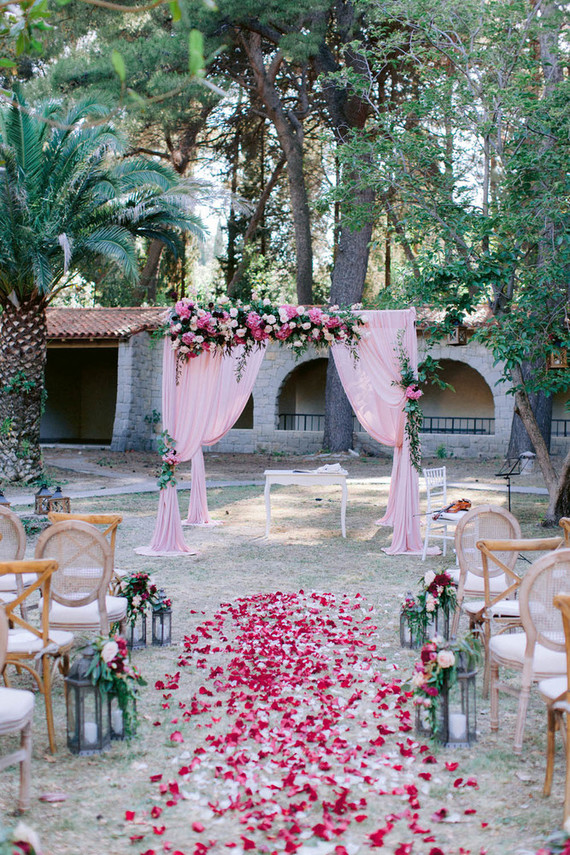 The wedding ceremony space was done with a bright pink wedding arch decorated with blooms and greenery, there were pink petals and lanterns