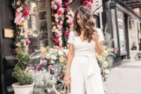 03 a casual white jumpsuit with a V-neckline, short sleeves, wideleg pants, nude shoes and a white bag