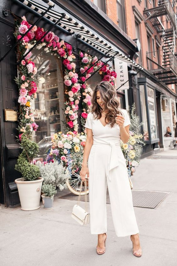 a casual white jumpsuit with a V-neckline, short sleeves, wideleg pants, nude shoes and a white bag