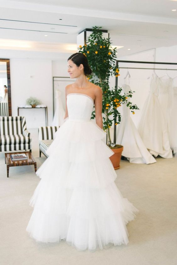 a classic wedding ballgown with a strapless embellished bodice and a tiered tulle skirt with a train