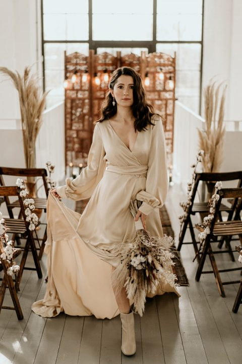 a neutral silk wrap wedding dress paired with tan suede booties and statement earrings are a trendy combo