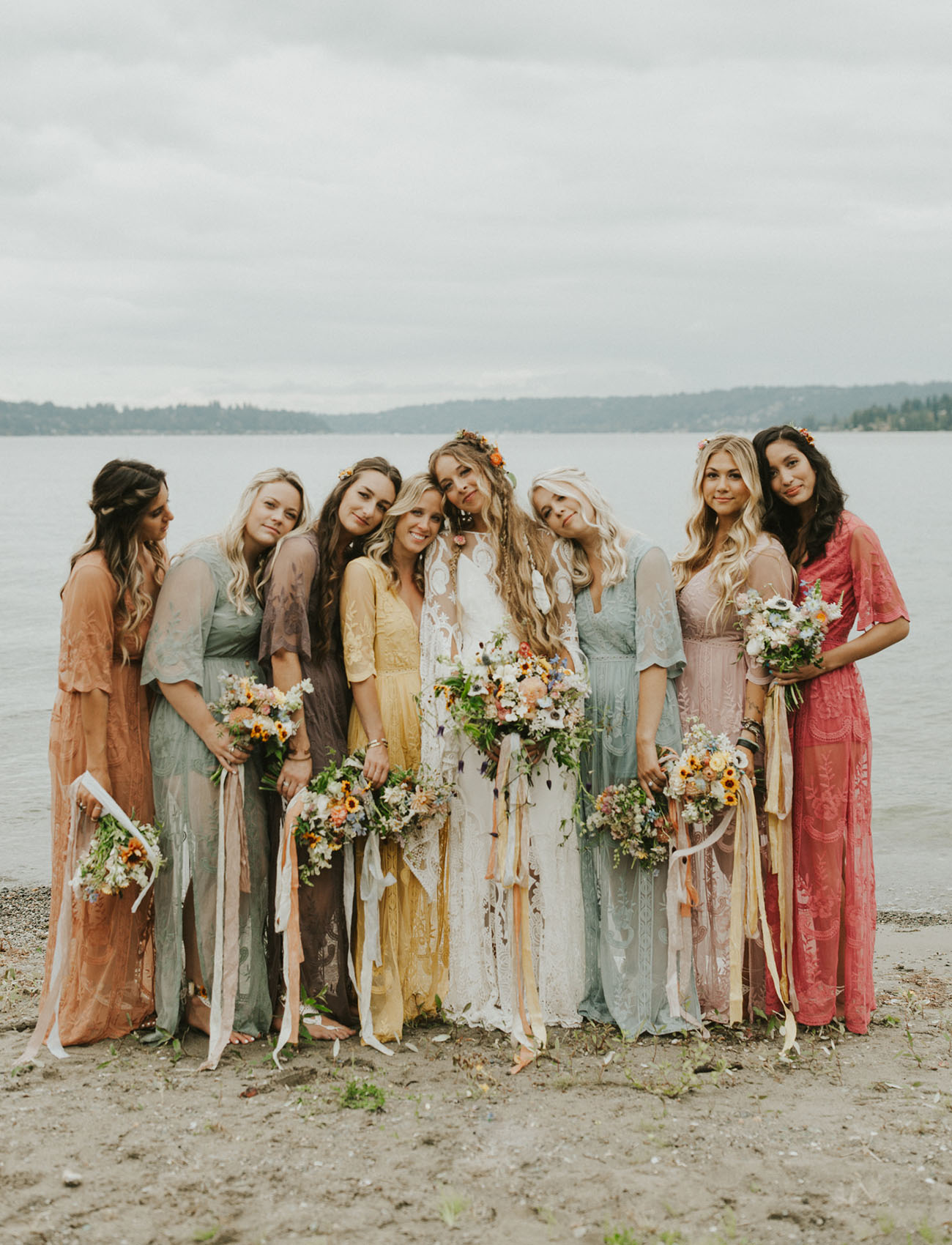 The bridesmaids were wearing pastel and muted color lace dresses and carrying similar bouquets