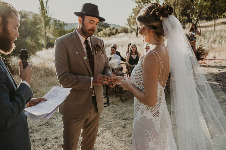 The groom was rocking a tan suit, a burgundy printed tie, a black hat