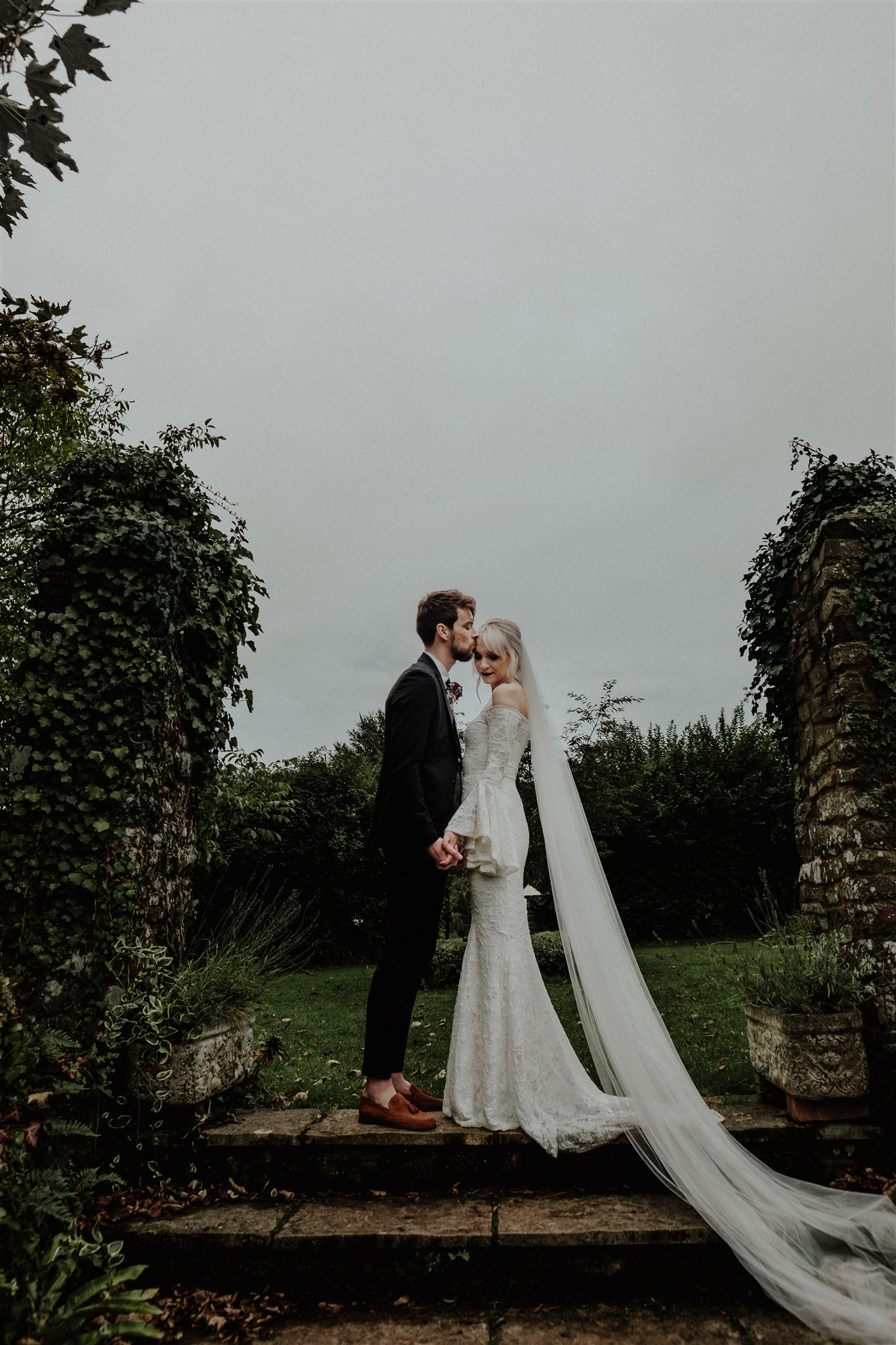 The groom was wearing a black suit, brown moccasins