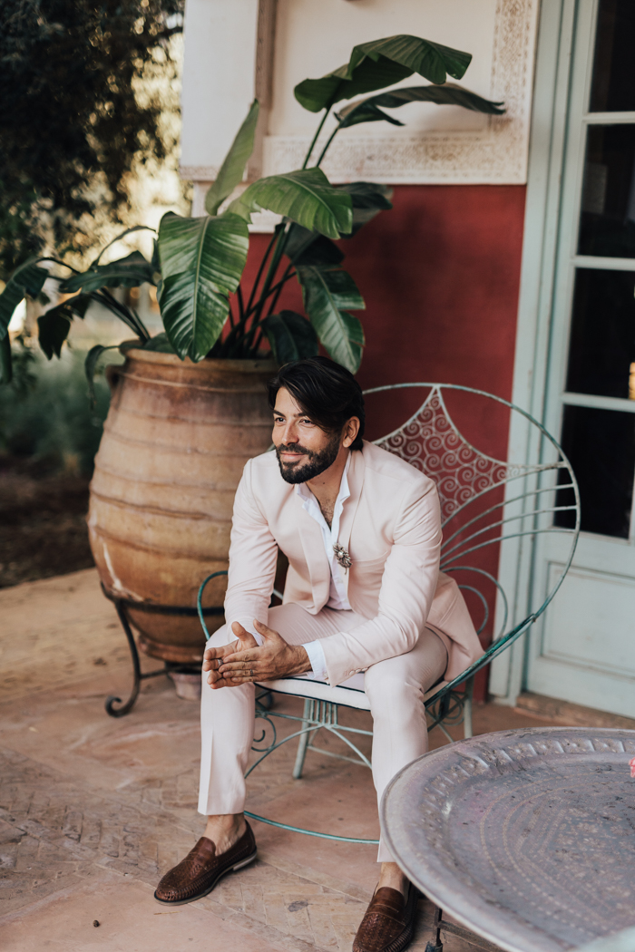 The groom was wearing a light pink suit, a white shirt, brown moccasins and a boutonniere