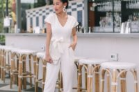 04 a casual white jumpsuit with a sash with a bow on the waist, nude shoes, statement earrings and a white clutch