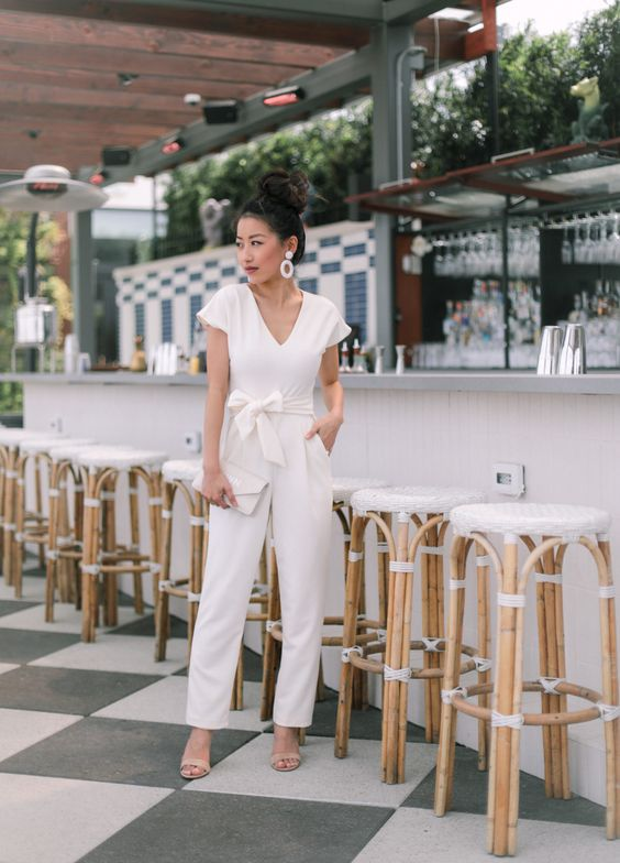 a casual white jumpsuit with a sash with a bow on the waist, nude shoes, statement earrings and a white clutch