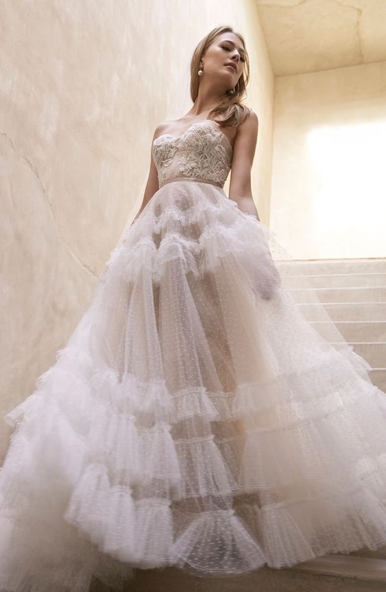 a romantic strapless A-line wedding dress wiht a lace embroidered bodice and a tiered tulle skirt wiht polka dots