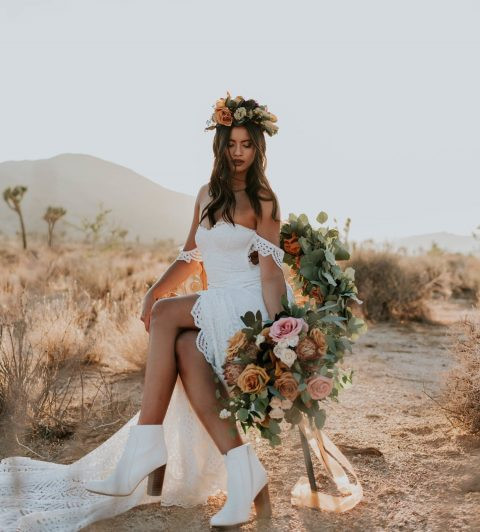 a white boho lace off the shoulder wedding dress with a long train and white booties