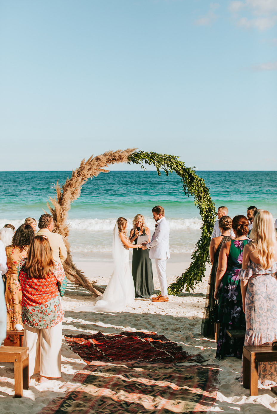 The wedding arch was a round one, of greenert and pampas grass plus boho rugs