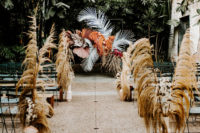 06 The wedding ceremony space was done with dried grasses, large tropical leaves and terra cotta vases