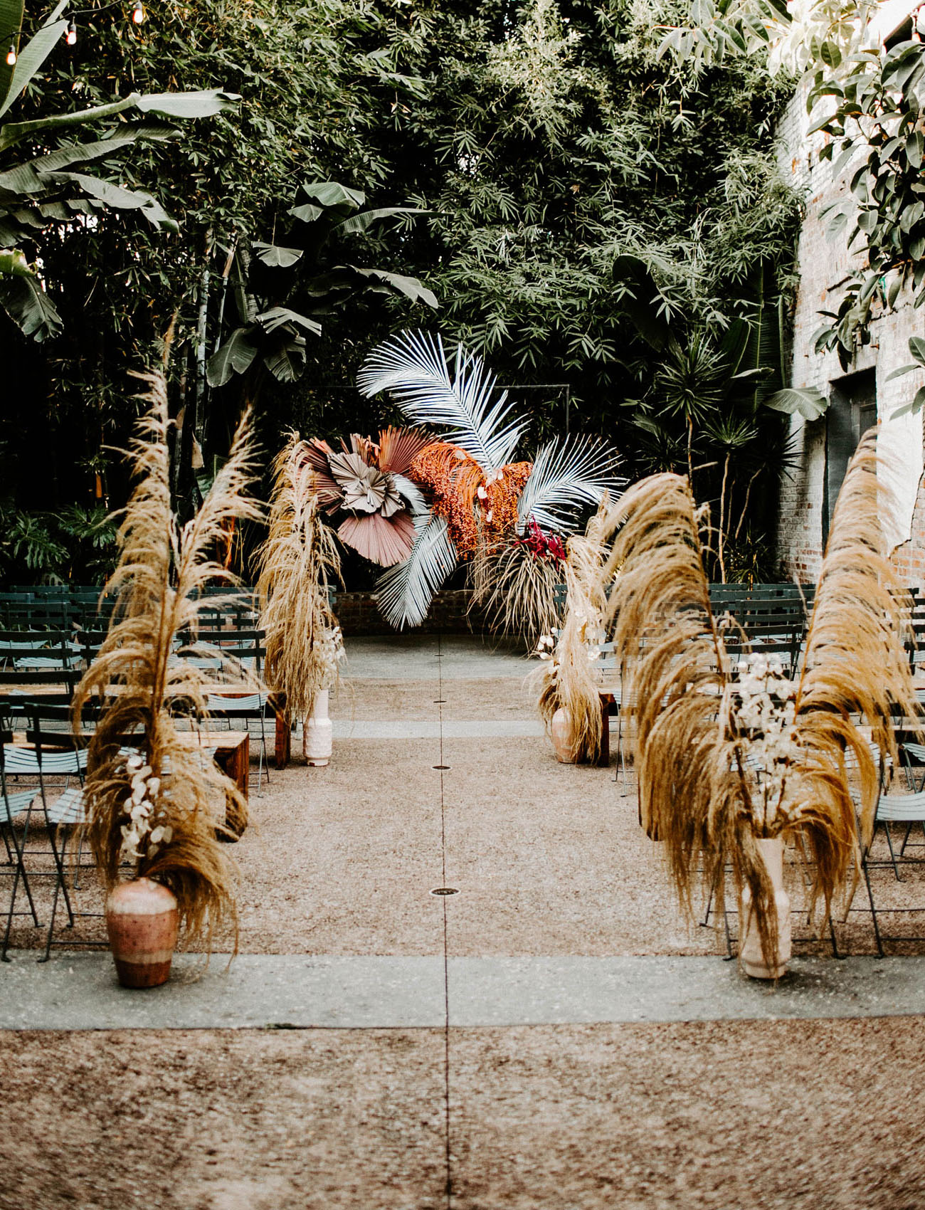 The wedding ceremony space was done with dried grasses, large tropical leaves and terra cotta vases