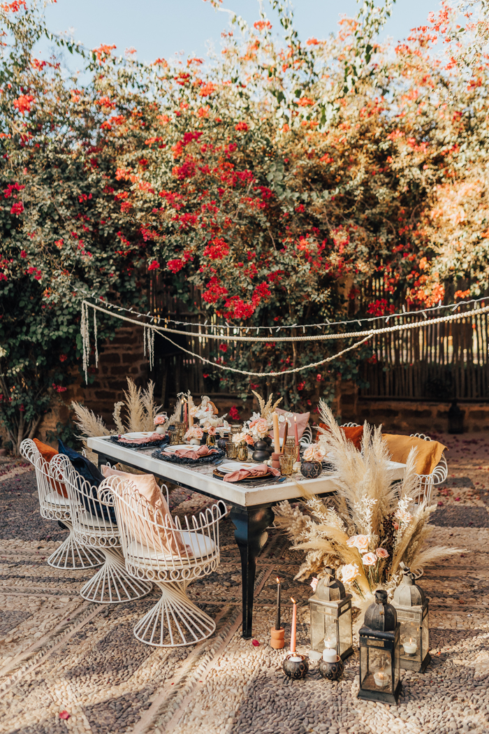 The wedding reception space was quirky and bold, with candle lanterns and pampas grass, blush blooms, black and dark chargers and cool chairs