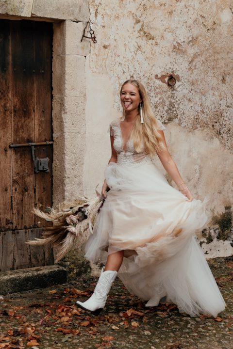 an A-line wedding dress with a lace bodice and a covered plunging neckline, white cowboy boots and statement earrings