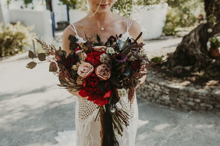 The wedding bouquet was dark, with bright and dark blooms and dried touches
