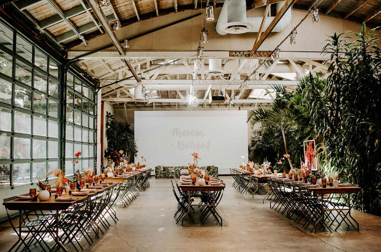 The wedding ceremony space was done with a tall greeneyr wall, bright blooms on the tables and dried grasses and fronds