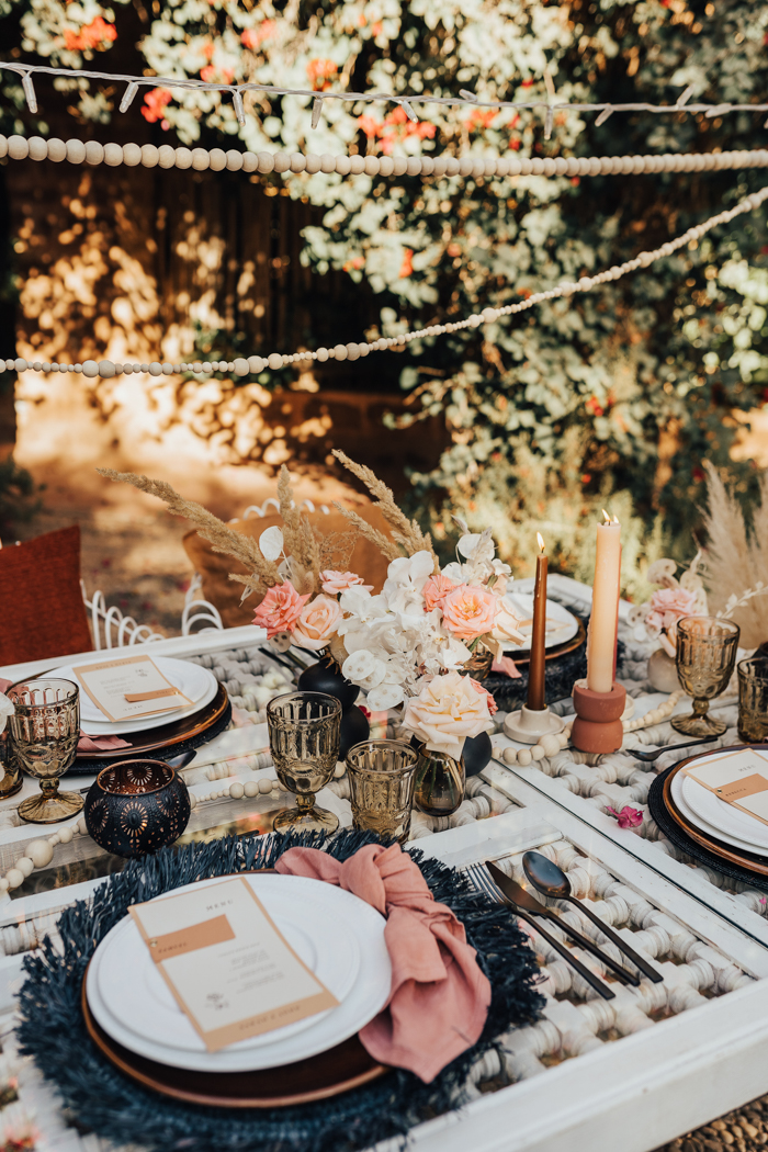 The wedding table was a woven one, with fringe chargers, peachy napkins, amber candles and black vases