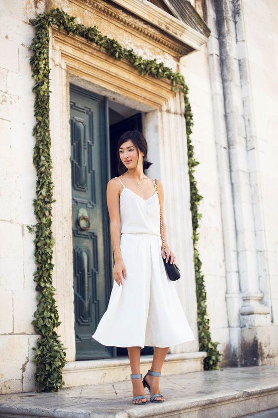 a white spaghetti strap top, white culottes, blue ankle strap shoes and a black bag for a casual feel