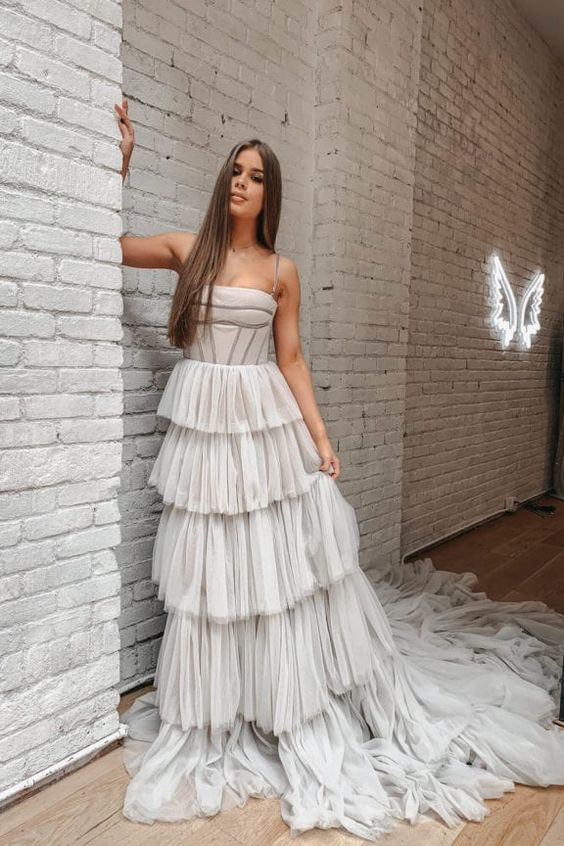 an off white modern romantic wedding dress with a corset-like bodice on spaghetti straps and tiered tulle skirt