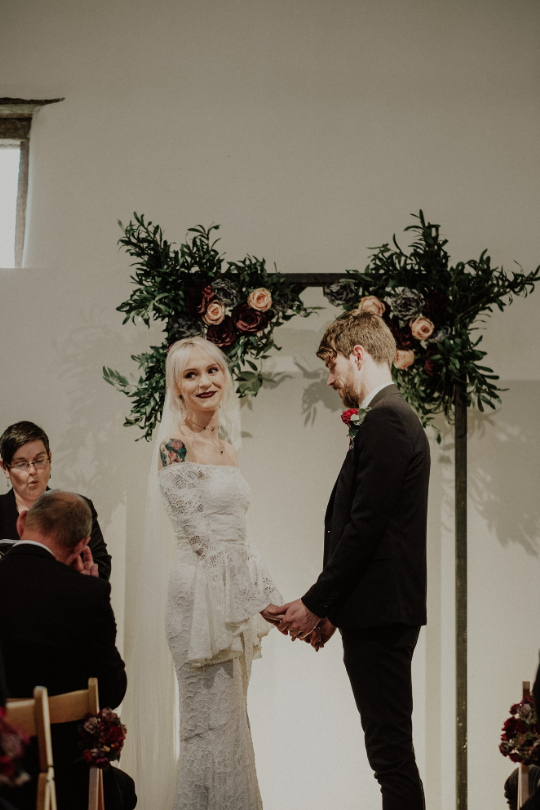 the ceremony was an indoor one, with a cute wedding arch decorated with blooms and greenery
