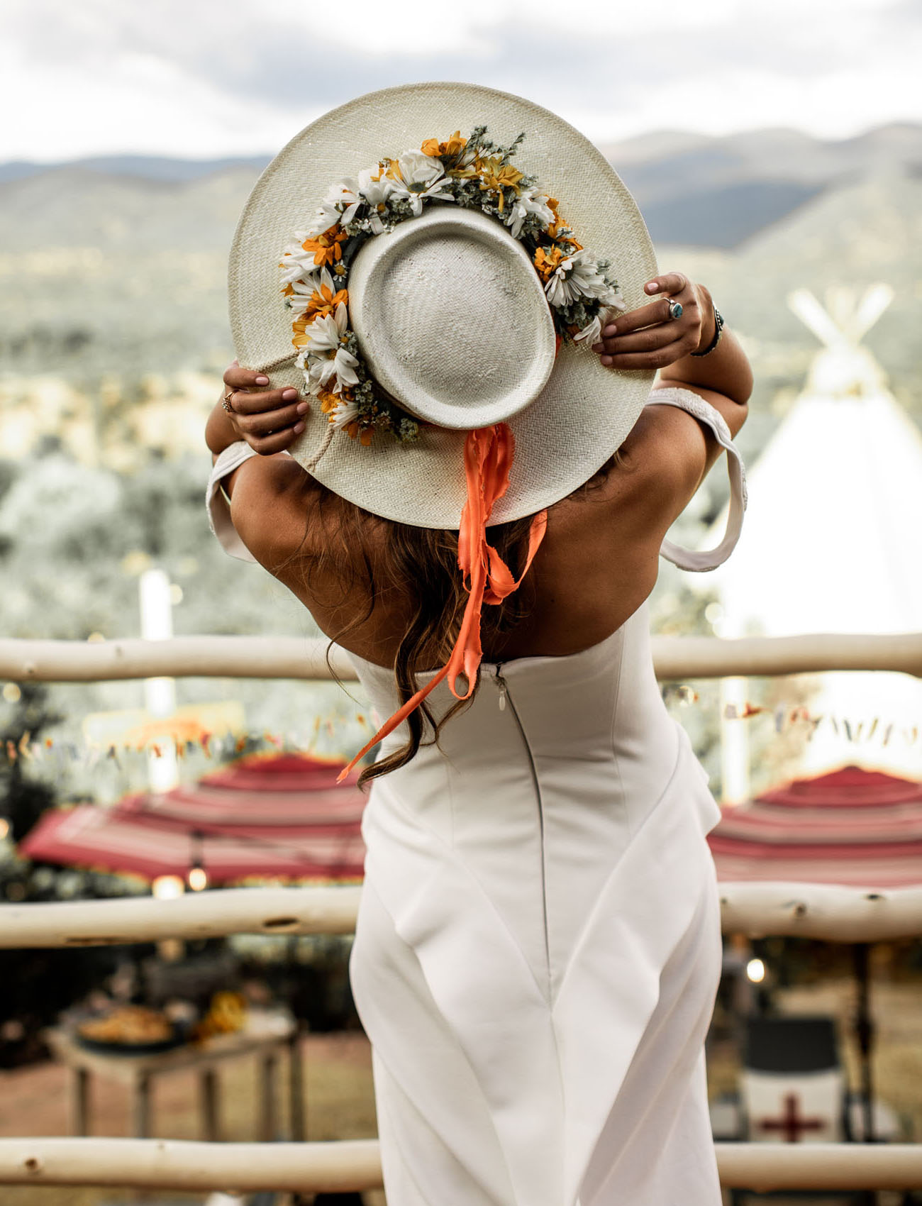 A floral hat is a nice accessory for a boho western bride
