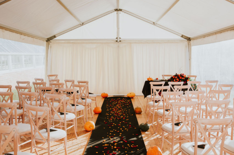 The ceremony space was light-filled, with a black runner, colorful petals and pumpkins as this was a Halloween wedding