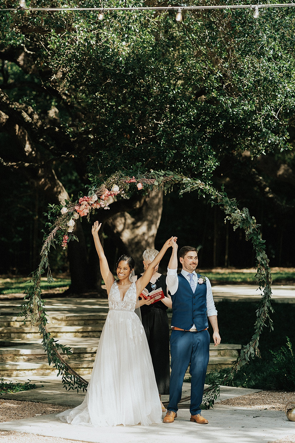 The wedding arch was done with greenery, pink and blush blooms