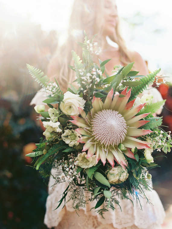 The wedding bouquet was done with lots of greenery, white blooms and a large king protea