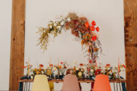 08 The wedding reception was done with a large overhead floral installation with dried leaves, with bright blooms on the table and a navy runner