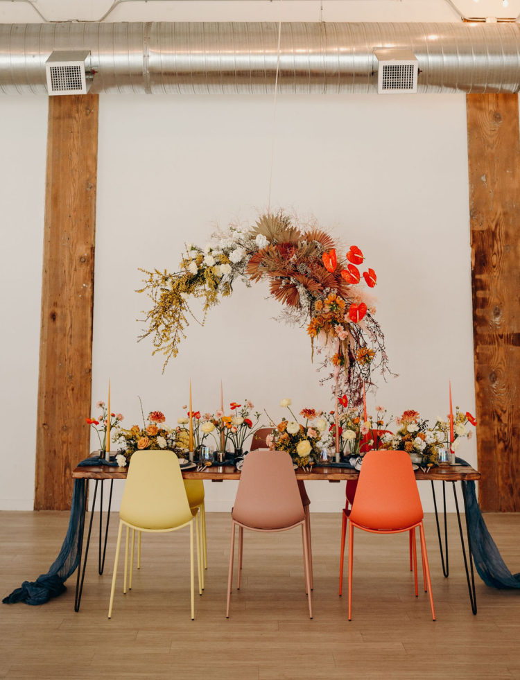 The wedding reception was done with a large overhead floral installation with dried leaves, with bright blooms on the table and a navy runner