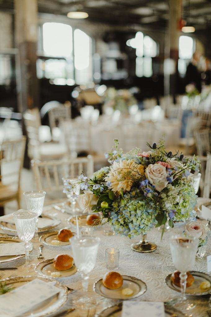 The wedding tables were done with lace tablecloths, pastel blue and neutral blooms and greenery
