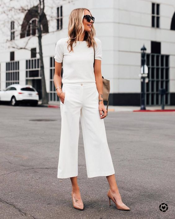 a white top with short sleeves, white culottes, blush shoes and a tan bag for a simple bridal shower look