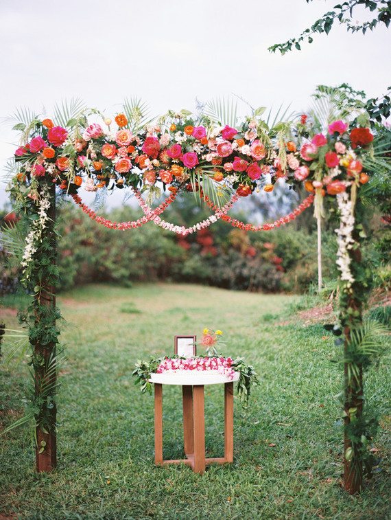 The wedding arch was decorated with lush greenery and bright red, pink and orange blooms