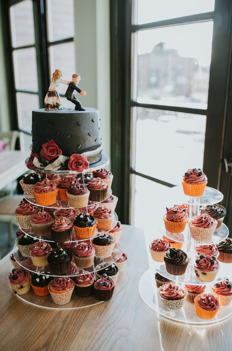 The wedding cake was black, with sugar blooms and funny toppers, and there were a lot of colorful cupcakes
