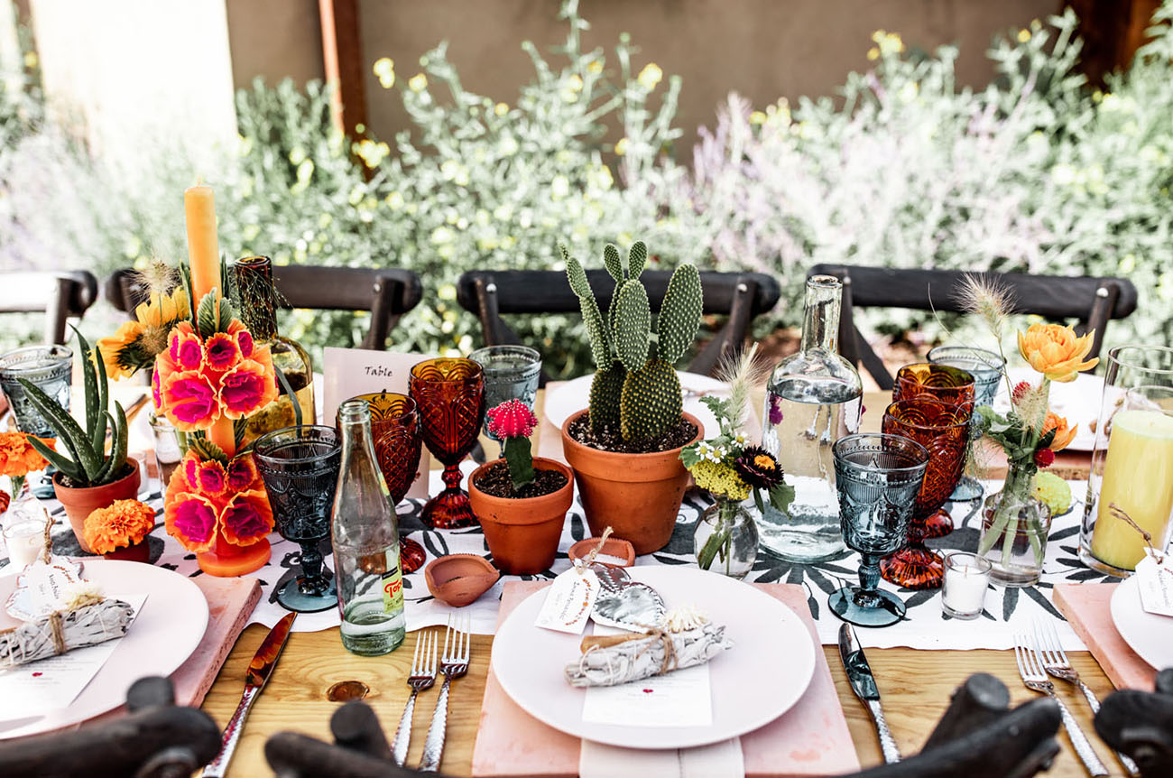 The wedding reception was done with bright blooms, cacti and pink placemats plus colroed glasses