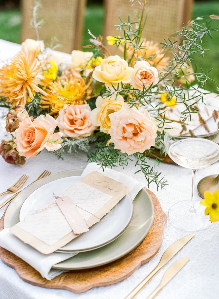The wedding tablescape was done with a wooden charger, pastel plates and bright blooms and greenery