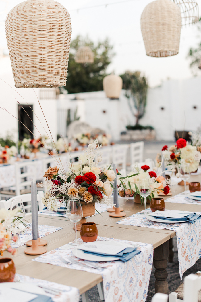 The wedding tablescapes were done with bright florals, grey candles and printed placemats