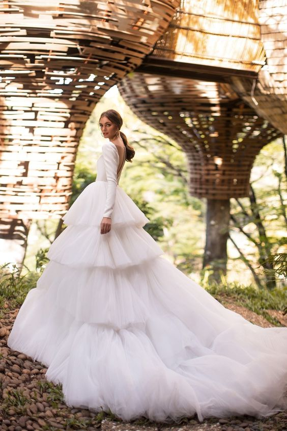 a modern wedding ballgown with a plain long sleeve bodice with an illusion back and a tiered tulle skirt with a train