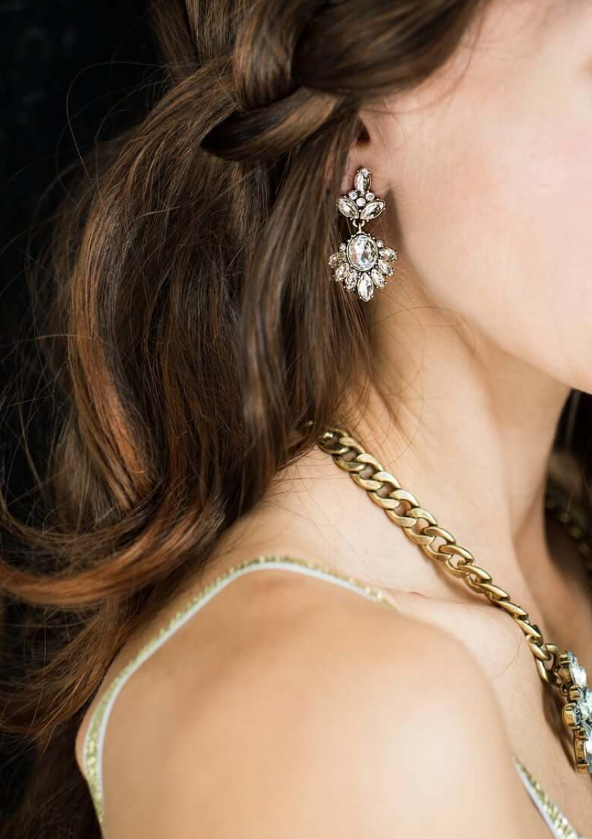 beautiful statement rhinestone earrings and a matching heavy chain necklace in gold are a bold idea