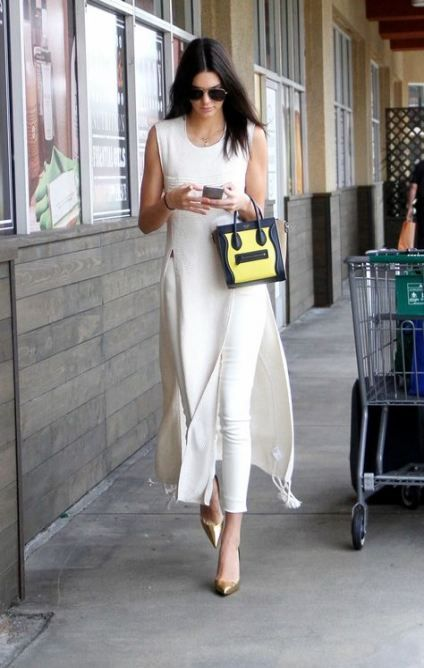 white skinnies and a sleeveless midi white dress with side slits, metallic shoes and a two tone bag